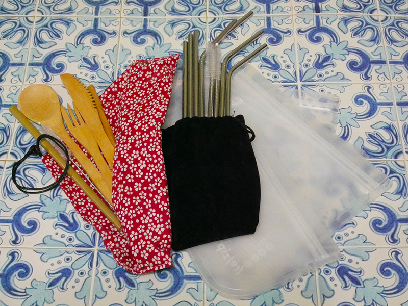 Shown in the photo is a bamboo utensil set that includes a fork, spoon, knife, chopsticks and straw in a red patterned carrying case, along with stainless steel straws and silicone food storage bags on a blue tiled background.  Single Use Plastics - IMG_4540