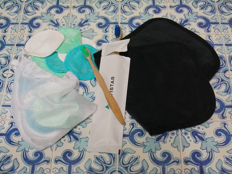Shown are reusable fabric makeup remover rounds, a reusable makeup remover towel and bamboo toothbrushes on a blue tiled background. Single Use Plastics - IMG_4542