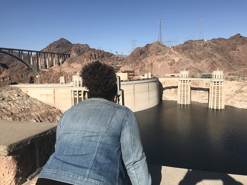 Ashley a.k.a girlwithherviews at the hoover dam overlooking the water from a tourist viewpoint